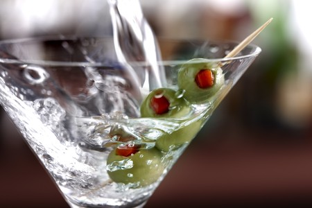Macro shot of vodka pouring into a martini glass with green olives