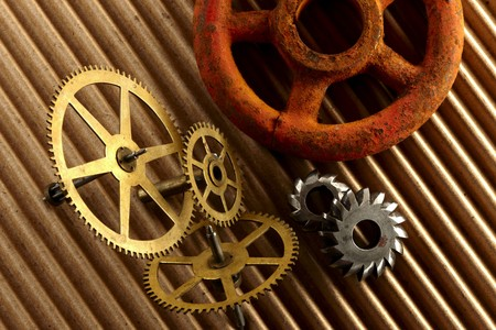 Gears and rusty old valve knob shot on brown corrrugated paper photo