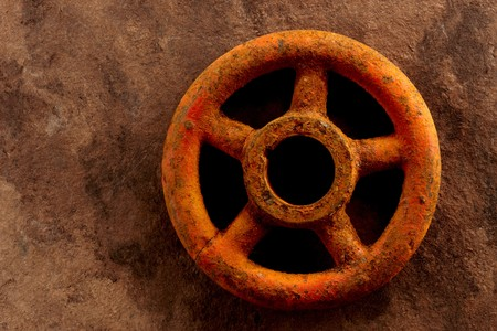 Rusty turn off valve shot on textured brown paper, with space for copy photo