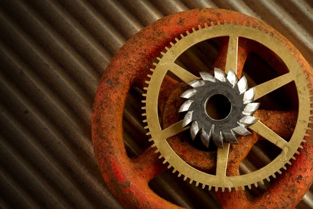 2 gears and a rusty old valve knob shot dramatically on brown corrrugated paper photo
