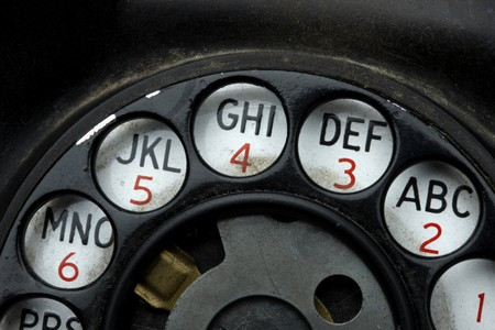 rotary dial telephone: Macro shot rotary dial on grungy, old telephone Stock Photo