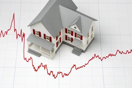 Modello di casa girato sul grafico raffigurante i tassi ipotecari Archivio Fotografico - 7244177