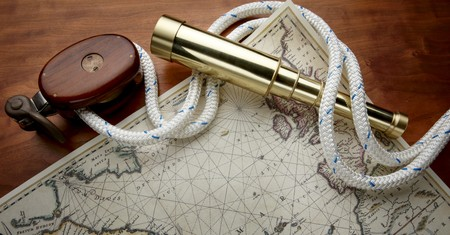 Wooden pulley, white nautical rope, antique, brass telescope and navigational map shot on boat deck