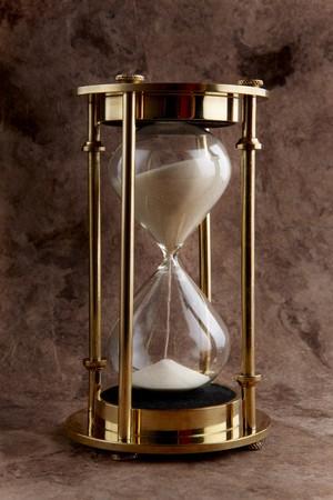 Brass hourglass shot on textured background Archivio Fotografico