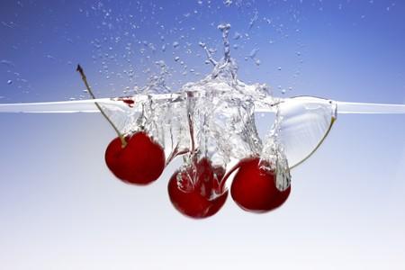 Close up shot of 3 cherries splashing into water photo