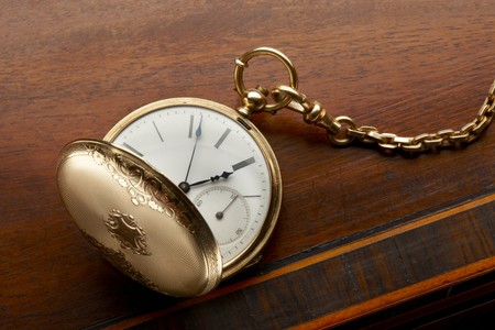 bezel: close up of opened antique pocket watch and chain shot on antique wooden surface, space for copy