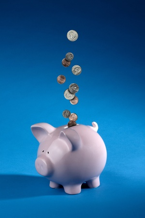 shiny American coins dropping into a pink piggy bank shot on blue background with space for copy