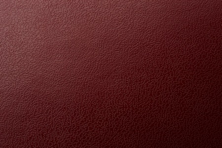Full frame of pebbly textured burgundy colored pleather