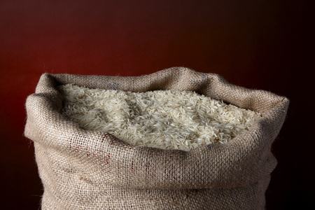 Sack of white rice in burlap sack shot in studio with space for copy photo