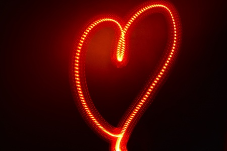 Shape of heart produced with moving red light, shot in studio includes space for copy