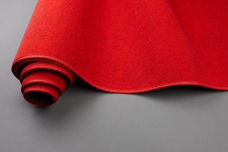 Closeup shot of a red carpet being rolled up, includes space for copy photo