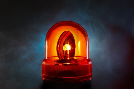 Bright red police light glows through a foggy night
