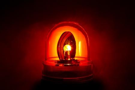 Close-up van een heldere rode politie licht geschoten door een rokerige nacht