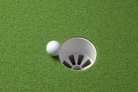 Close up shot of golf ball rolling to the rim of a hole, with space for copy photo