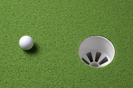 Close up shot of a golf ball a few inches from the hole with space for copy photo