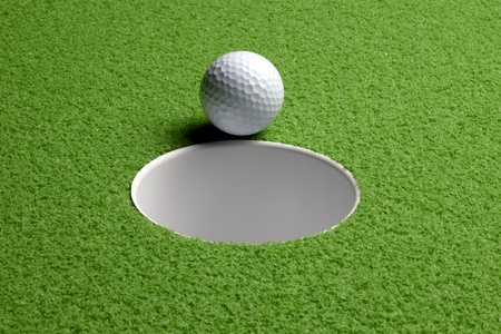 Close up shot of golf ball about to drop into hole, includes space for copy