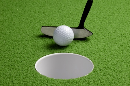 Close up shot of putter tapping in a golf ball on the green photo