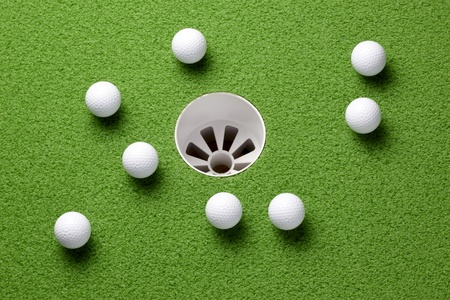 Several golf balls near hole on putting green Archivio Fotografico