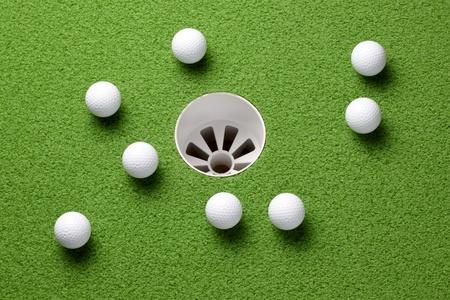 Several golf balls near hole on putting green photo