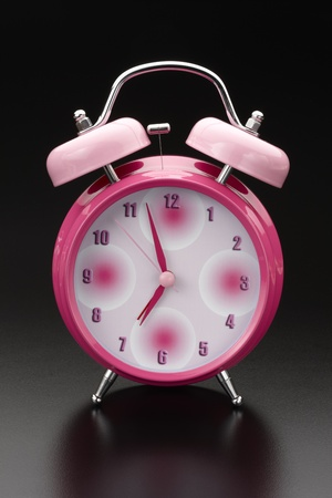 Classic pink ink alarm clock shot on reflective background with space for copy photo