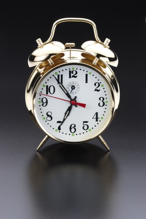 Klassieke gouden wekker geschoten op reflecterende achtergrond