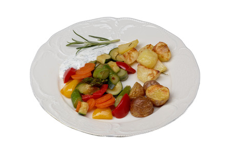 oven potatoes: isolated plate with vegetables and oven potatoes Stock Photo
