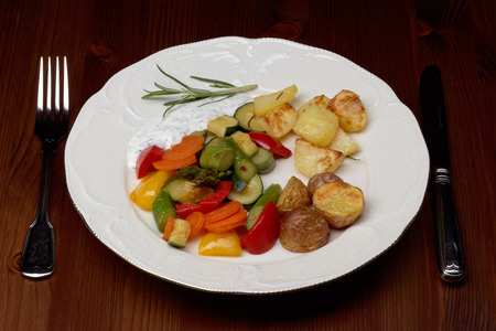 plate with vegetables and oven potatoes photo