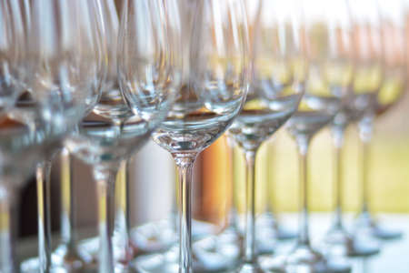 shallow  focus: Wine glasses shallow focus blurred foreground defocused background bokeh light optical refraction sun flares. Stock Photo