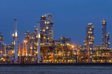 oil refinery: A petrochemical plant, with its stainless steel cylinders, its valves, chimneys, pipes, tubes and construction artificially lit just before the break of dawn