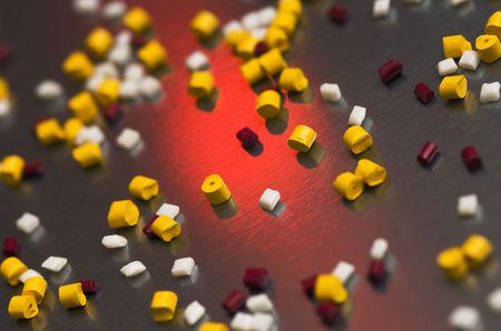 extruded: Vari tipi di estrusi e triturati polimero grani su un foglio di acciaio, retroilluminato da un rosso strobo