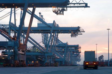 La automatizado de carga y descarga de buques contenedores en la terminal de contenedores de Rotterdam continuar el d�a y la noche; las enormes gr�as de espera para los pr�ximos portacontenedores \ 'llegada.  Foto de archivo - 2067248