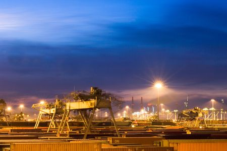 Night scene of a container terminal, with fully automated cranes moving through the vast rows of containers.