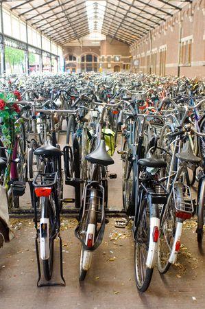 handle bars: Filas y filas de bicicletas aparcadas en una estaci�n de tren.  Foto de archivo