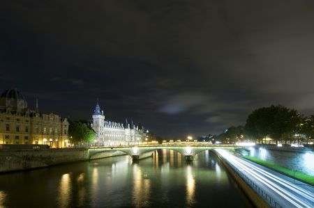lightbeam: Bridges over the River Seine in Paris, with the Conciergerie on the Ile de la Cite nicely lit. A patch of clouds is lit with a lightbeam from below, just above the horizon