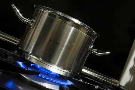 centered: Stainless steel pan on a burning stove heated by a gas flame Stock Photo