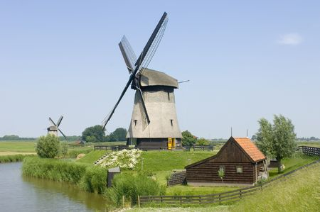archetypal: The archetypal image of the Netherlands; a quaint scene, with a barn, two windmills, and a lush, reed covered canal, meandring through the rural landscape Stock Photo