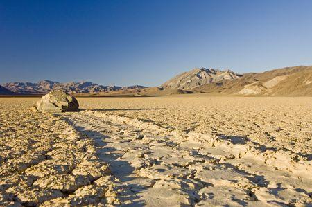 현상: The phenomenon of the moving rocks at Death Valley Race Track Playa. The setting sun casts a shadow over the near by rock, still basking the mountains in the background in a warm glow 스톡 사진