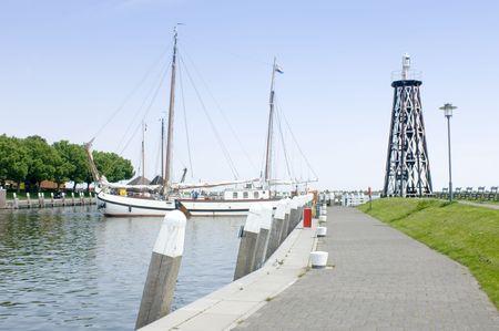 ijsselmeer: A huge flatbottom boat manouvering itself inside the Enkhuizen harbor entrance on the IJsselmeer coast in the Netherlands