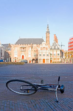 at town square: The empty town square, early morning, with an abandoned bicycle and the sun-lit town hall in the background Stock Photo