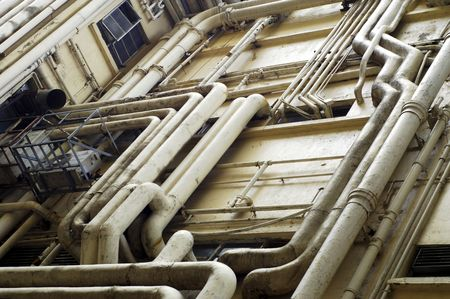 The chatotic and excessive plumbing of a Hong Kong residential building on the exterior with tubes for electricity, water and airconditioning
