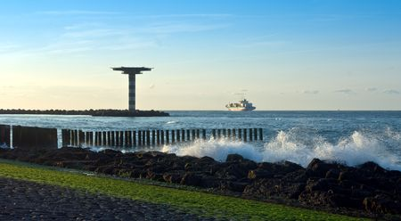seafreight: A container ship leaving port on a tranquil evening, sailing past a helicopter platform