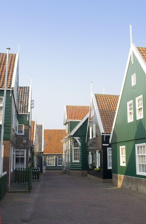 archetypal: The typical style Dutch fishermans houses on the Peninsula of Marken. The quaint wooden gables, and the archetypal green and white paint in a deserted street during a summer evening.