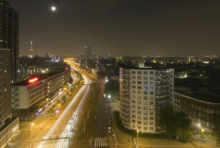 euromast: Midnight traffic in Rotterdam, the Netherlands, seen from above. The moon and the Euromast are in view, the suburbs and residential areas on the right