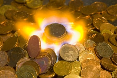 burning money: A glowing red hot coin in front of the blue flames of burning natural gas, a metaphor of wasting energy, not only bad for the environment, but also a waste of money