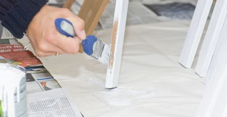 priming brush: A female hand putting a primer on wooden beams. Focus on the tip of the brush