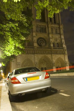 notre dame: A sports car parked illeally at night in front of the Notre Dame Cathedral in Paris, in a spot reserved for taxis. The police car in front is issuing parking tickets while another car passes by Stock Photo