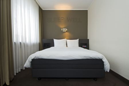 sleep well: The interior of a modern, stylish hotel room with a double bed, drawn curtains, a night light and an alarm clock and the text Sleep Well in relief on the wall Stock Photo