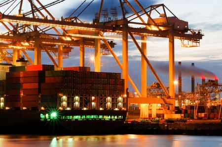 seafreight: The motion and activity of a container terminal at dusk, with all fascets of the harbor: the ships, the containers, the cranes, the carriers, the processing industry.