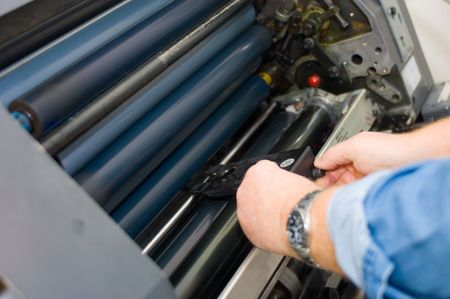 offset: Adjusting the sheet feeder height of a printing press Stock Photo