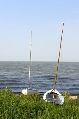 ashore: Two sailing  boats ashore on the banks of the IJsselmeer, the Netherlands on a summer evening
